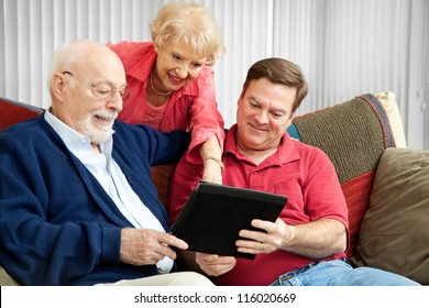 Adult son and elderly parents using their tablet PC at home.