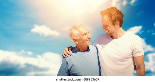 Adult son hugging his old father against cloudy sky with sunshine