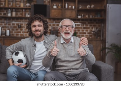 adult son hugging senior father while showing thumbs up at home