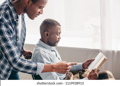 adult son looking at senior father reading book in wheelchair