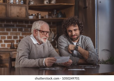 adult son and senior father looking at old photos at home