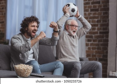 adult son and senior father watching football game and showing yes signs at home