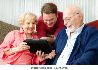 Adult son teaching his parents to use their new tablet pc computer.