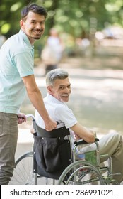 Adult son walking with disabled father in wheelchair at park.