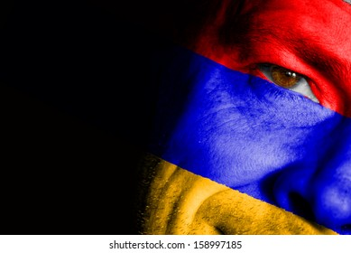 An adult sports fan with his face painted in the colors of the Armenia's flag