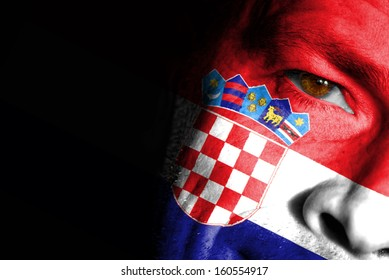 An adult sports fan with his face painted in the colors of Croatia's flag