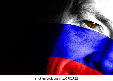 An adult sports fan with his face painted in the colors of the Russian Federation's flag