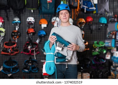 Adult sportsman chooses a sports equipment in the sports store