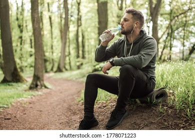 Adult sporty man in forest, park  in the morning