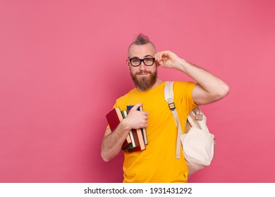 Adult student cheerful casual wear guy with beard and backpack holding books isolated on pink background