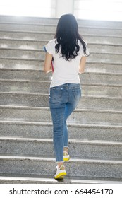 adult student walking at stairs in campus,rear view