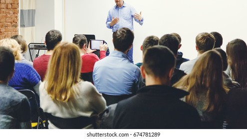 Adult students listen to professor's lecture in small class room. Rear view, panoramic aspect ratio.