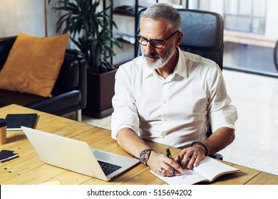 Adult successful businessman wearing a classic glasses and working at the wood table in modern coworking studio.Stylish bearded middle age man making notes notebook. Horizontal,blurred background