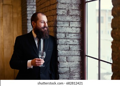 Adult successful elegant businessman with beard wearing suit and drinking wine.