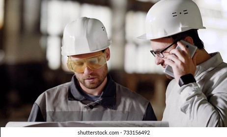 Adult superintendent and architect in protective helmets on the head call a smart phone to the customer of the project, in order to approve changes in the existing plan of building modernization
