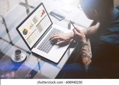 Adult tattooed businessman working on mobile computer at sunny office.Man typing on notebook keyboard.Graphs and diagramm on laptop screen.Horizontal,blurred background