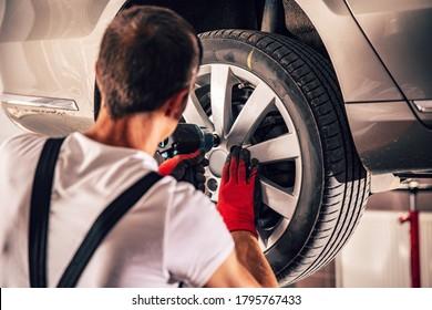 Adult technician adjusting car's tire in workshop