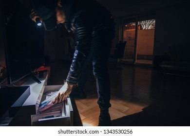 Adult thief wearing black looting from the desk in living room, motion blur