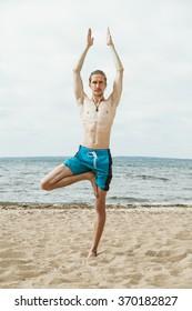 Adult thin man with naked torso doing yoga on the beach. Vrikshasana pose