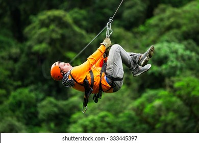 Adult Tourist On Zip Line Dressed In Orange Against Green Background