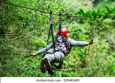 Adult Tourist Wearing Casual Clothing On Zip Line Trip Selective Focus Against Blurred Forest