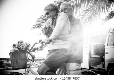 adult two team enjoy and have fun outdoor holiday playing with old bike. vitage retro van in background. nice retired concept under the backlight sun . hug together and laughing.  tiny house and cute