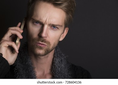 Adult unhappy man with mobile phone in hand