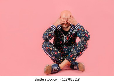 Adult unhappy sad bald depressed man in fashionable trendy tracksuit isolated on pink background.  Conceptual psychological portrait of stylish despaired boy siiting on ground indoor. Odd crying boy