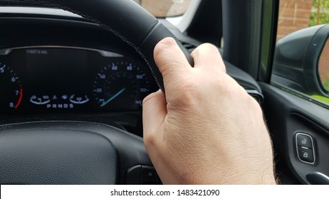 Adult white Caucasian male with a partially amputated left hand index finger holds steering wheel of a car.