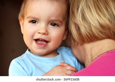 Adult white woman (grandmother) holding cute child boy who is hugging her and looking out behind her back, close-up emotional portrait, indoor