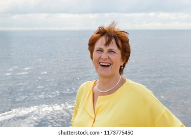 adult white woman on a sea background laughing, portrait of an elderly woman in a yellow blouse,