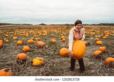 Adult woman (30s) attempts and struggles to lift and to pick up a giant pumpkin from a pumpkin patch. Smiling and laughing and having fun