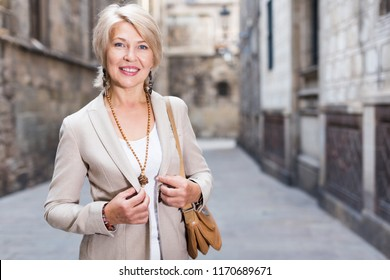 Adult woman 50s years old is walking in classic dress in old city.