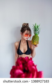 Adult woman in bikini with pineapple and sunglases. Peony flower on foreground.