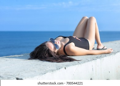 Adult woman in bodysuit lying on seafront. Thirty-year-old woman in black bodysuit and tinted sunglasses lying on back on concrete seafront