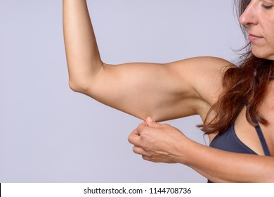 Adult woman with brown hair stretching under arm skin as she flexes muscle over plain white background