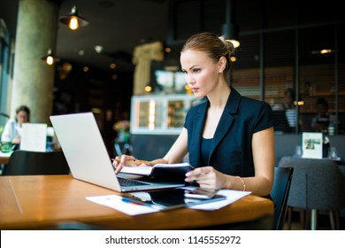 Adult woman business worker searching financial information on web site via laptop computer, sitting in restaurant. Female skilled entrepreneur checking online e-mail via netbook. Economist using apps