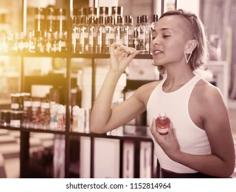 Adult woman buyer choosing bottle of pheromones in the sex shop