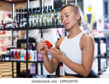 Adult woman buyer choosing bottle of pheromones in the sex shop