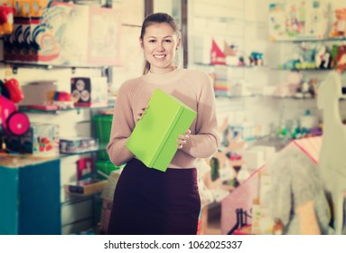 Adult woman buyer with color box among children's toys in the store