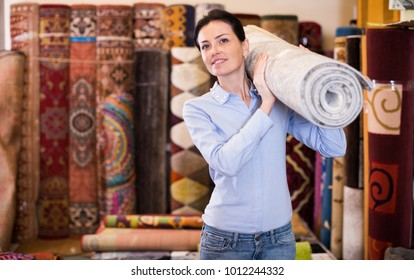 Adult woman buyer standing and choosing in shop with colour carpets