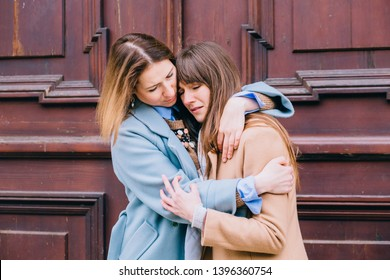 Adult woman calming her friend outdoor. Female consoling crying female sister. Mature mother and adult daughter outside.