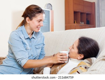 Adult woman caring for sick mature mother in living room at home