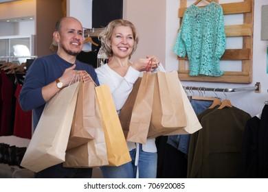 Adult woman chooses clothes at shop