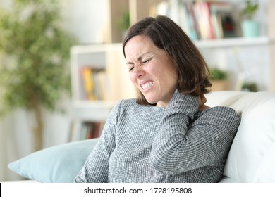 Adult woman complaining suffering painful nechacke sitting on a couch at home