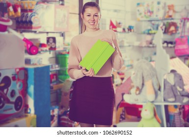 Adult woman consumer with color box among children's toys in the store