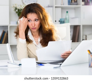 Adult woman is crying because of problems with documents in the office.