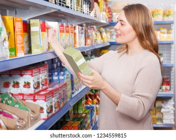 Adult woman customer choosing groats in  grocery food store