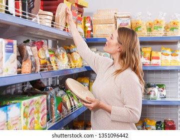 Adult woman customer choosing wafers in  grocery food store
