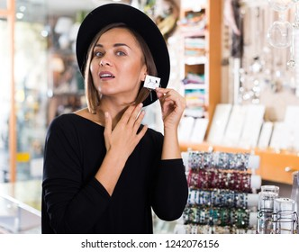 Adult woman customer in hat trying earrings in the shop of bijouterie